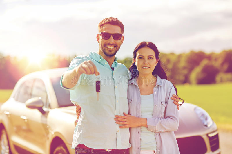 Happy man and woman with car key hugging. Transport, road trip, travel, family and people concept - happy men and women with car key hugging stock photography