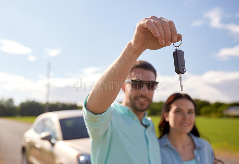 Happy man and woman with car key outdoors. Transport, road trip, travel, family and people concept - happy men and women with car key outdoors royalty free stock photos