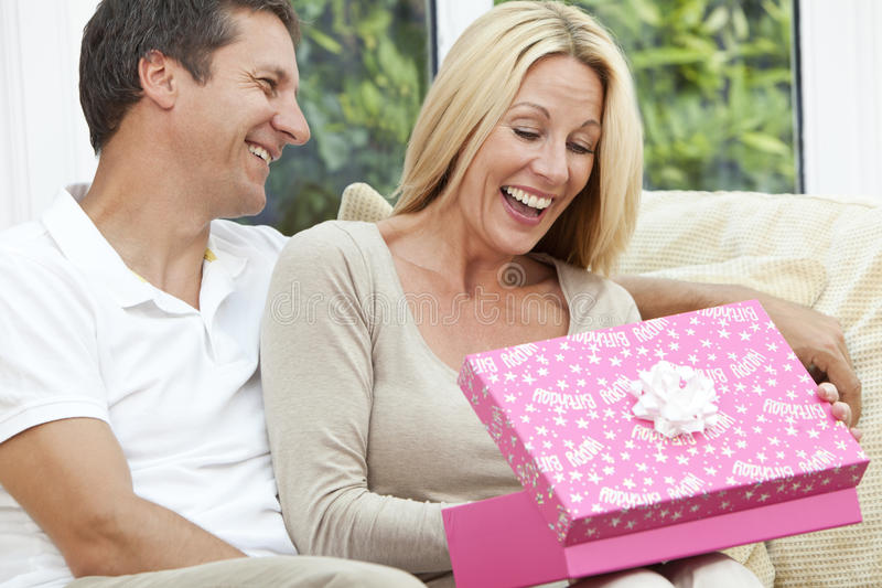 Happy Man & Woman Couple Opening Birthday Present. Attractive, successful and happy middle aged men and women couple in their forties, celebrating her birthday stock images