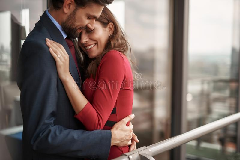 Happy man and woman having romantic meeting outdoor. Concept of romantic engagement. Waist up portrait of happy beloved couple clinging together with love and stock photos