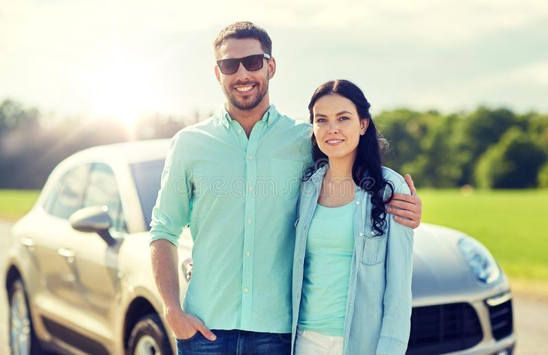 Happy man and woman hugging at car. Transport, road trip, travel, family and people concept - happy men and women hugging at car royalty free stock photography