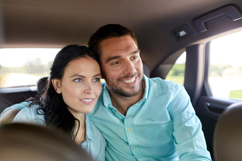 Happy man and woman hugging in car. Transport, road trip, travel, family and people concept - happy men and women hugging in car stock image