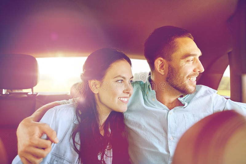 Happy man and woman hugging in car. Transport, road trip, travel, family and people concept - happy men and women hugging in car and looking to window royalty free stock photo