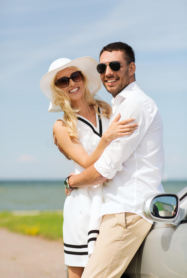 Happy man and woman hugging near car at sea. Transport, travel, love, date and people concept - happy men and women hugging near cabriolet car at sea side stock photo