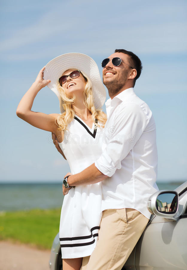 Happy man and woman hugging near car at sea. Transport, travel, love, date and people concept - happy men and women hugging near cabriolet car at sea side stock image