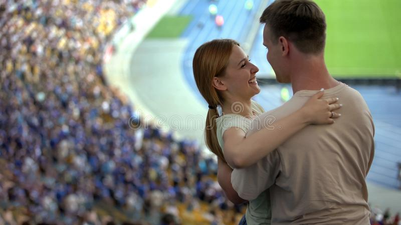 Happy man and woman hugging and smiling at stadium, football fans date, love stock image