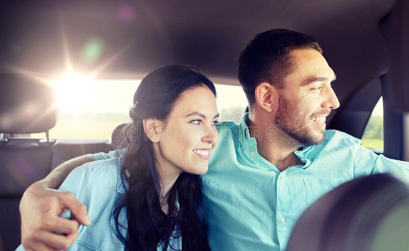 Happy man and woman hugging on taxi back seat. Transport, road trip, travel and people concept - happy men and women riding on a back seat of taxi car and stock photography