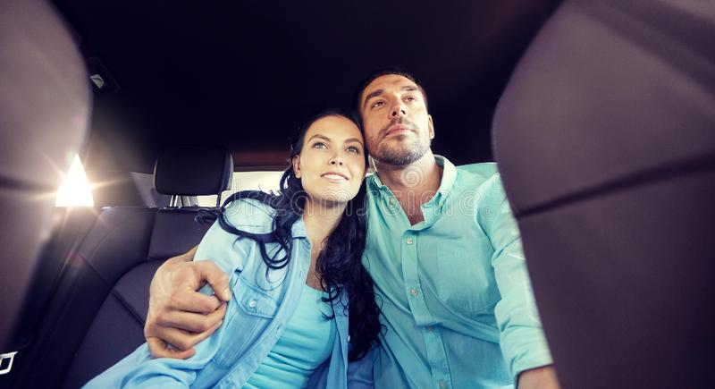 Happy man and woman hugging on taxi back seat. Transport, road trip, travel and people concept - happy men and women riding on a back seat of taxi car and royalty free stock images