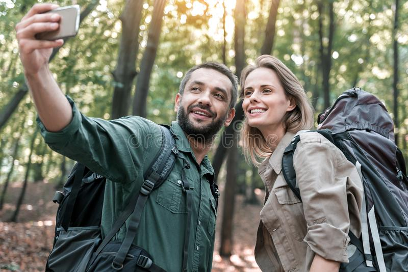 Happy man and woman photographing themselves on smartphone in nature stock image