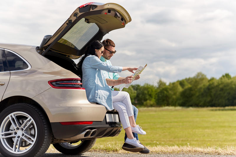 Happy man and woman with road map at hatchback car stock images