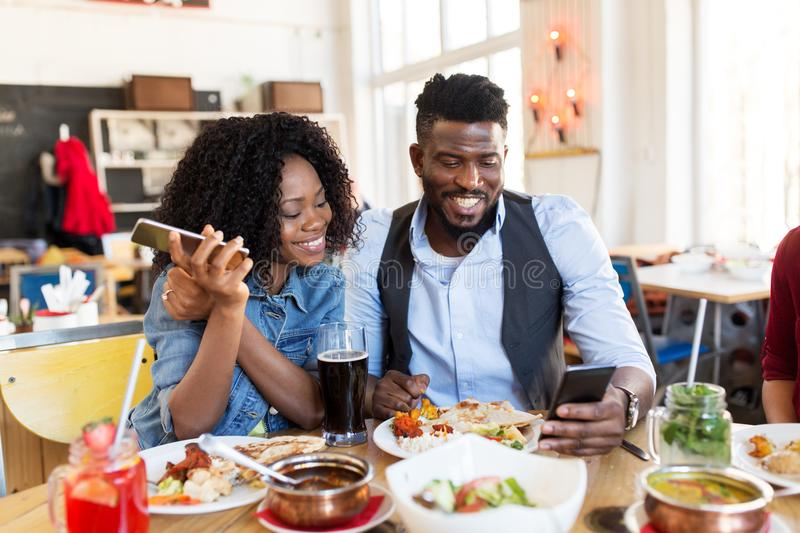 Happy man and woman with smartphones at restaurant. Leisure, technology and people concept - happy men and women with smartphones eating at restaurant stock photo