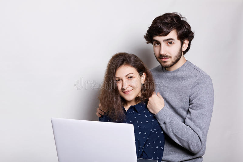 A happy man and woman standing sideways with laptop looking directly into camera over white background. Stylish guy with royalty free stock images