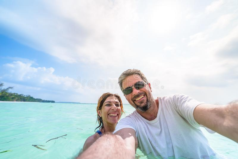 Happy man and woman taking selfie in tropical caribbean sea. Adult mid age traveling couple, real people having fun in vacation royalty free stock image