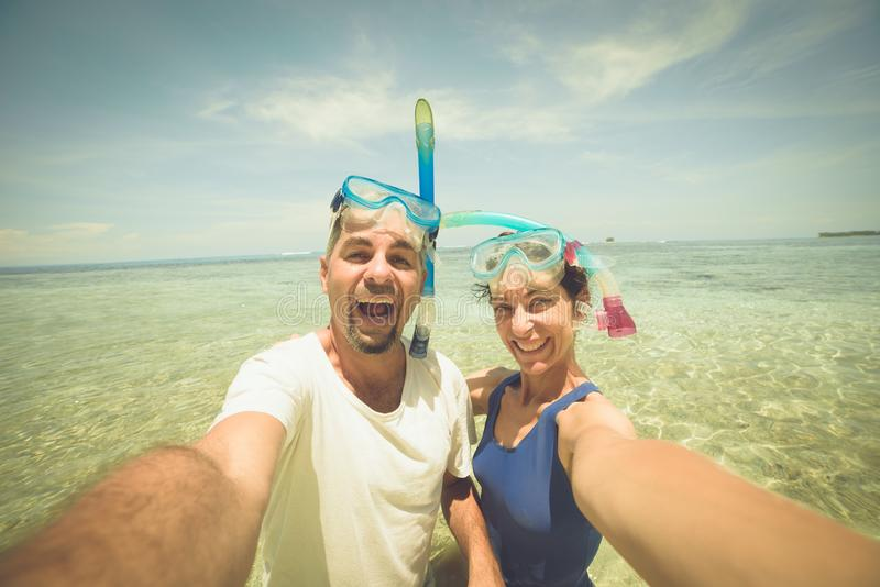 Happy man and woman taking selfie wearing snorkeling mask in tropical caribbean sea. Adult mid age traveling couple, real people royalty free stock image