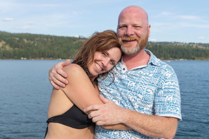 Happy Man and Woman together at a lake. Happy couple together on a lake royalty free stock image