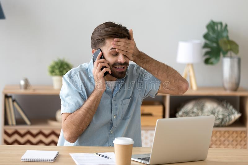 Happy man working feel relieved hearing good news over cell stock photo