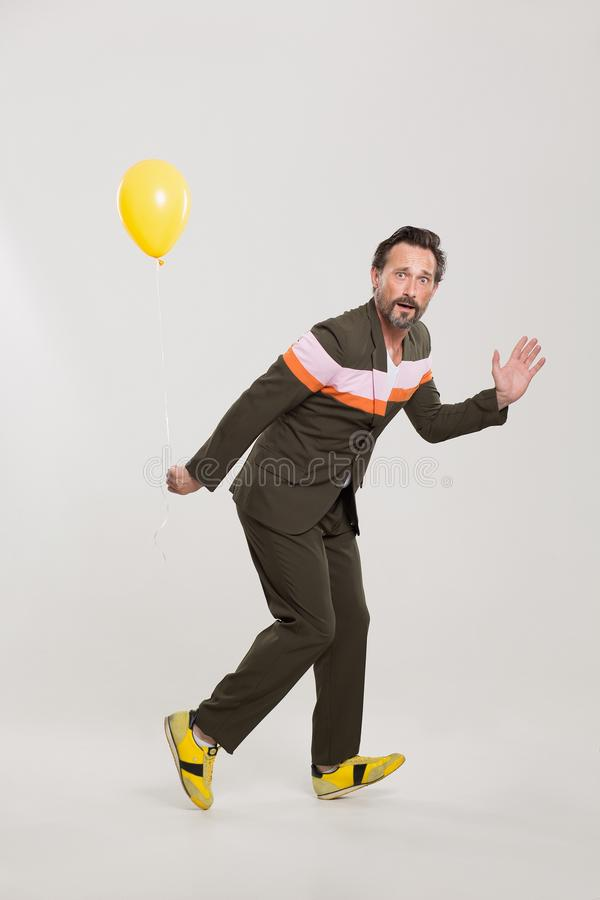 Happy man with yellow balloon. Handsome man in black suit with colorful stripes. Holding yellow balloon royalty free stock photography