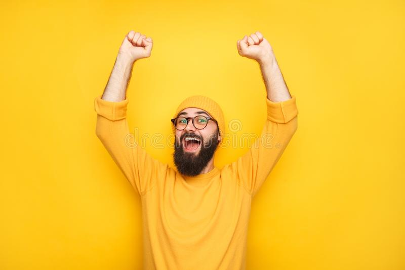 Happy man in yellow with hands up stock photos