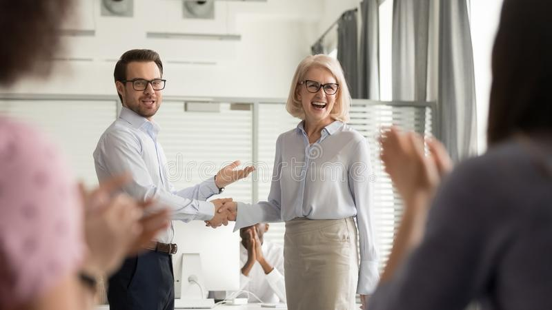 Happy manager boss praising old employee get team appreciation stock photography
