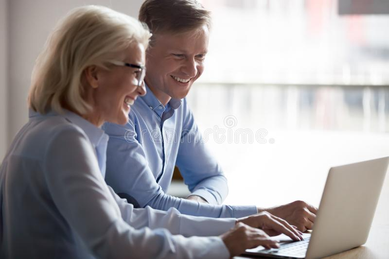 Happy manager and client having conversation at meeting with laptop stock photos