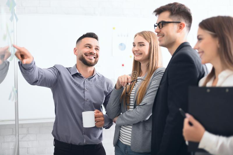 Happy manager explaining business strategy to staffs royalty free stock photos
