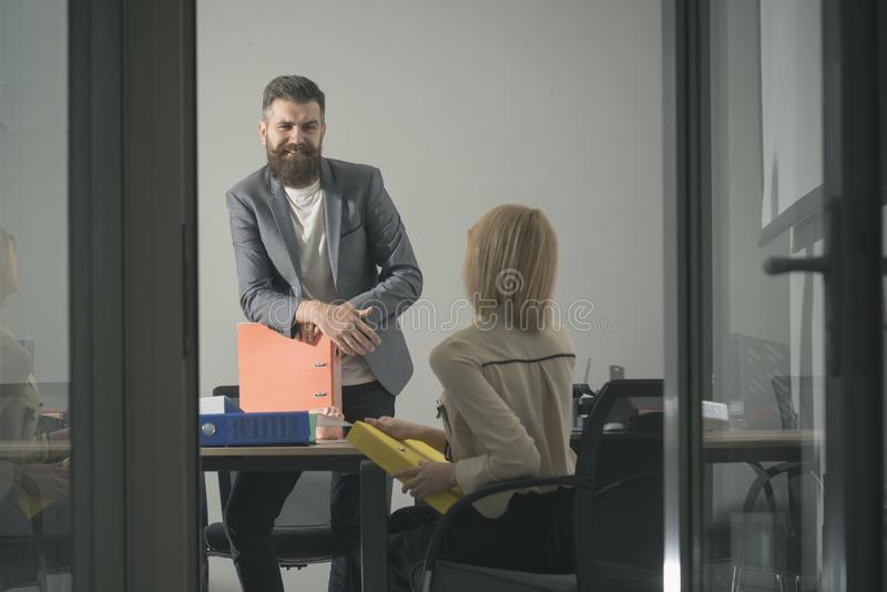 Happy manager smile at financier in office. Bearded man and woman discuss financial report. Businessman and royalty free stock photo