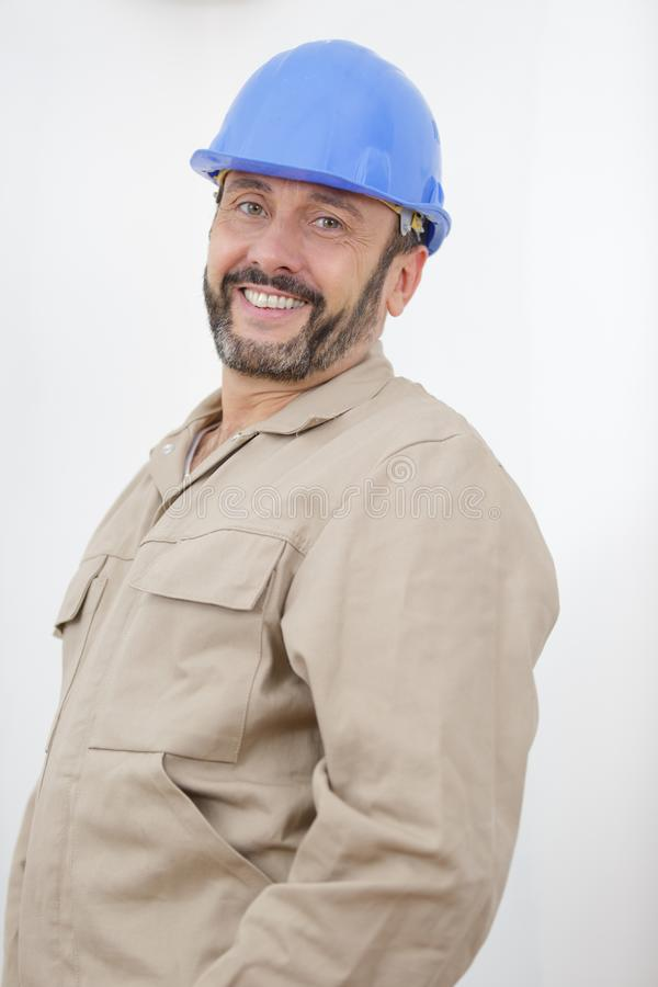 Happy manual worker standing inside. Man royalty free stock photos