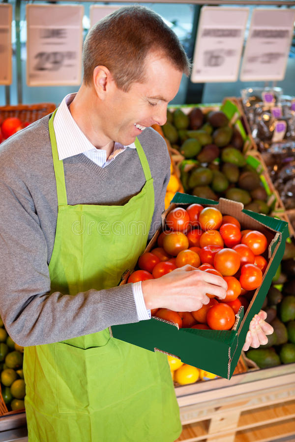 Happy market assistant holding box of tomatoes stock photo