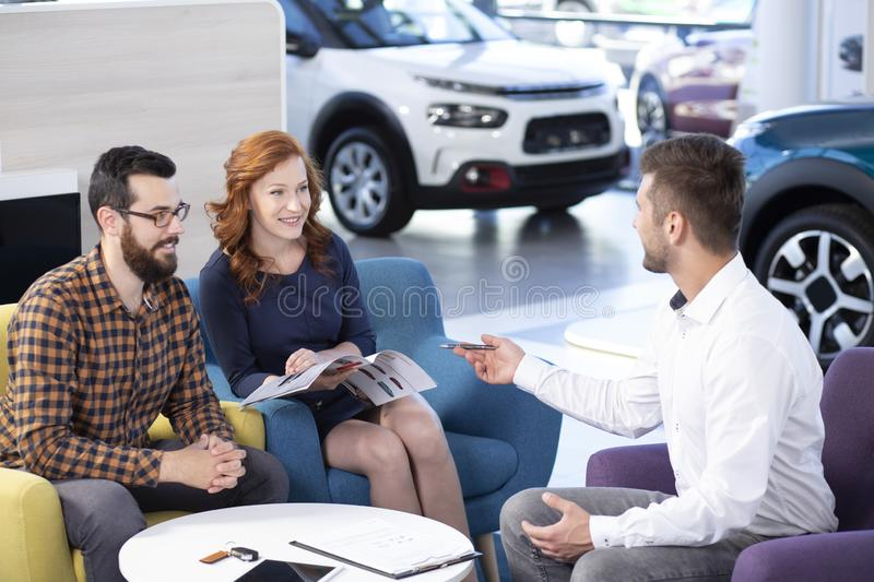 Happy marriage buying new car while talking with seller in a dea stock photography