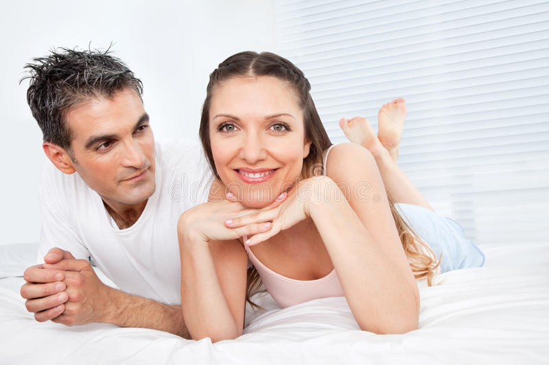 Happy married couple in bed royalty free stock image