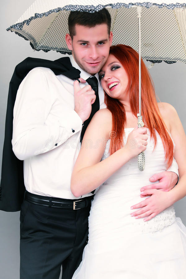 Happy married couple bride groom on gray background. Wedding day. Portrait of happy married couple red haired blue eyed bride and groom with umbrella studio shot royalty free stock images