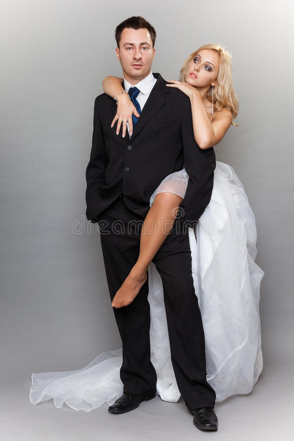 Happy married couple bride groom on gray background royalty free stock photography