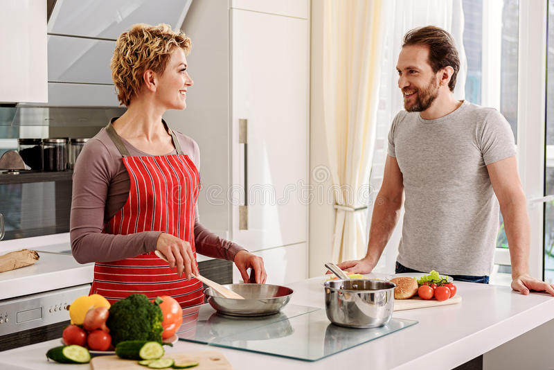 Happy married couple cooking in kitchen. Joyful women is preparing lunch for her husband. She is looking at men with love and smiling royalty free stock image