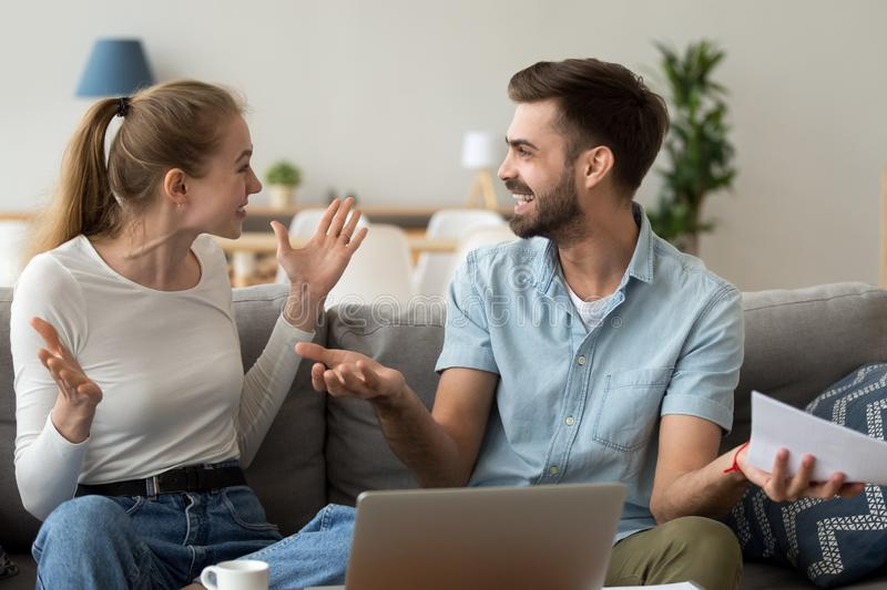 Happy married couple excited by receiving good news about finance. Income or refund, using laptop in living room, online banking, husband holding paper stock photography