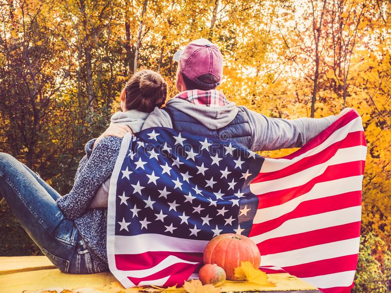 Happy married couple holding the US flag. Against the background of yellow trees and the setting sun. Happy relationship concept royalty free stock photos