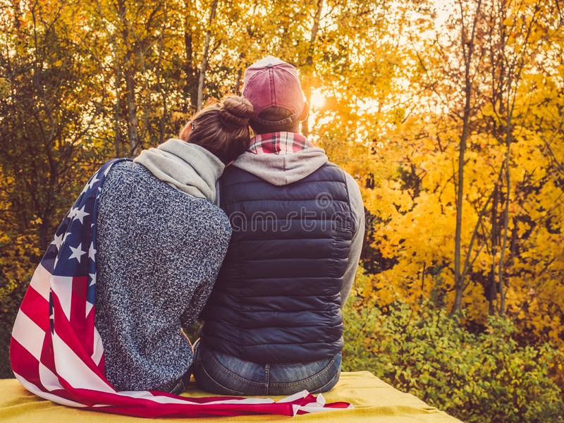 Happy married couple holding the US flag. Against the background of yellow trees and the setting sun. Happy relationship concept stock photos