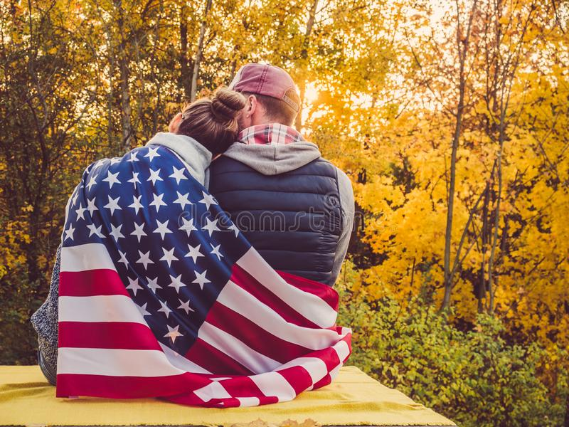Happy married couple holding the US flag. Against the background of yellow trees and the setting sun. Happy relationship concept stock images
