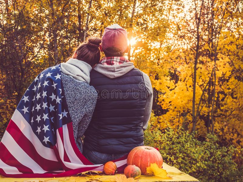 Happy married couple holding the US flag. Against the background of yellow trees and the setting sun. Happy relationship concept stock photography