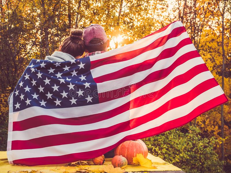 Happy married couple holding the US flag. Against the background of yellow trees and the setting sun. Happy relationship concept royalty free stock image