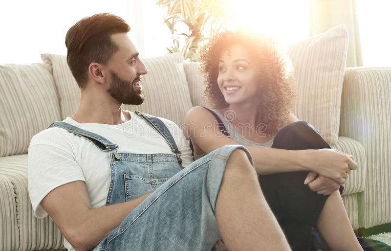 Happy married couple sitting on the carpet in a new apartment. stock photography