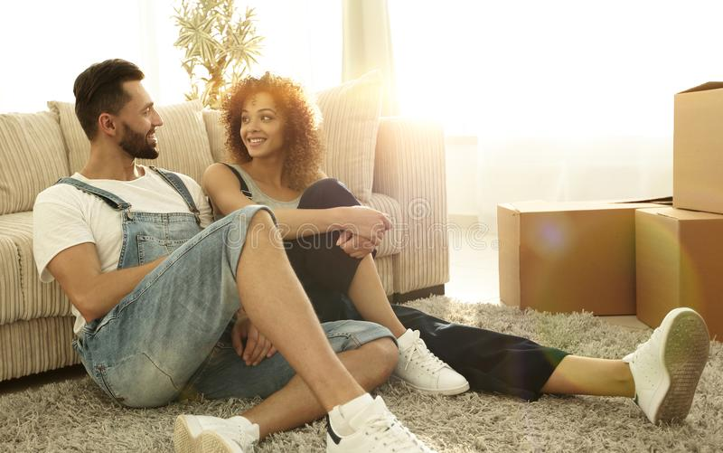 Happy married couple sitting on the carpet in a new apartment. royalty free stock photos
