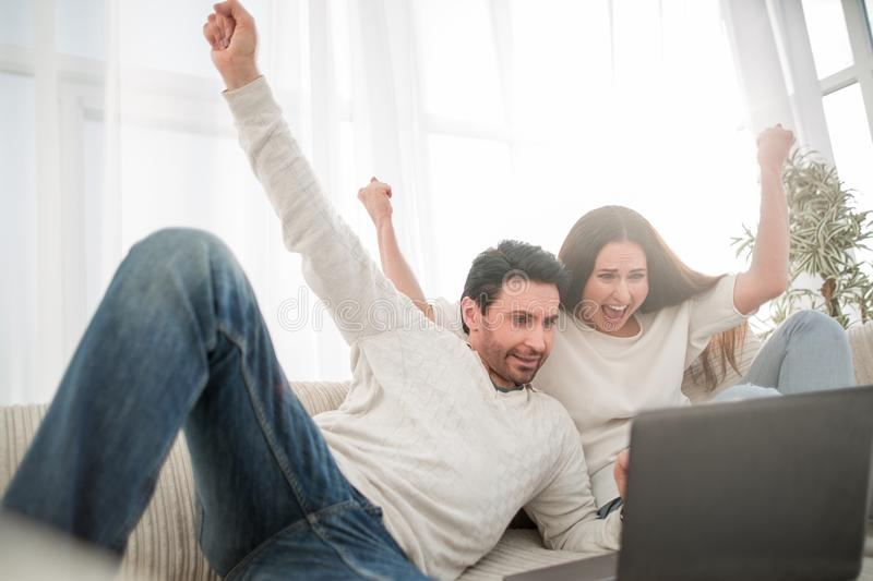 Happy married couple sitting on the couch. stock photos