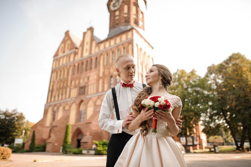 Happy married couple with a wedding bouquet standing in background of beautiful building royalty free stock images