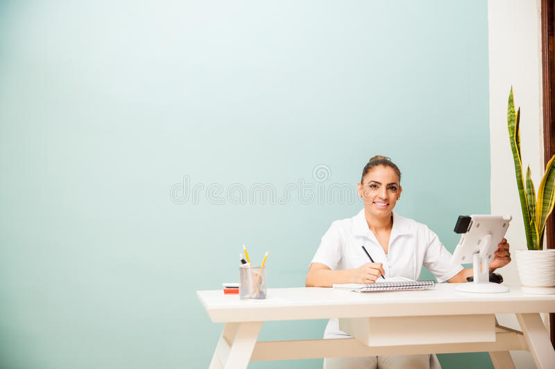 Happy masseuse at a front desk stock photos