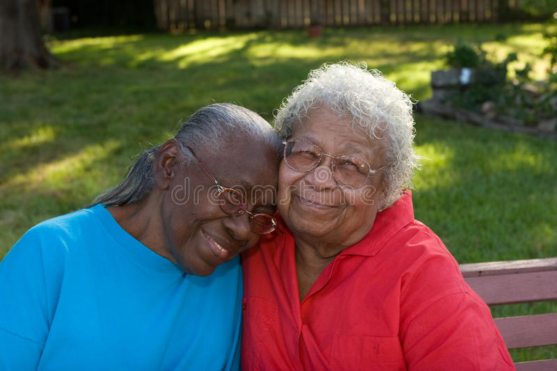 Happy mature African American sisters laughing and smiling. royalty free stock photography