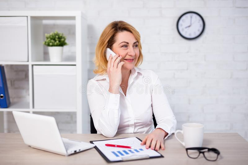 Happy mature business woman sitting in office and talking by phone stock photos