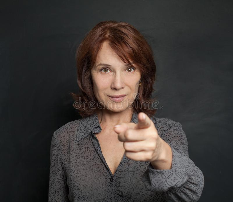 Happy mature business woman smiling and pointing royalty free stock photos