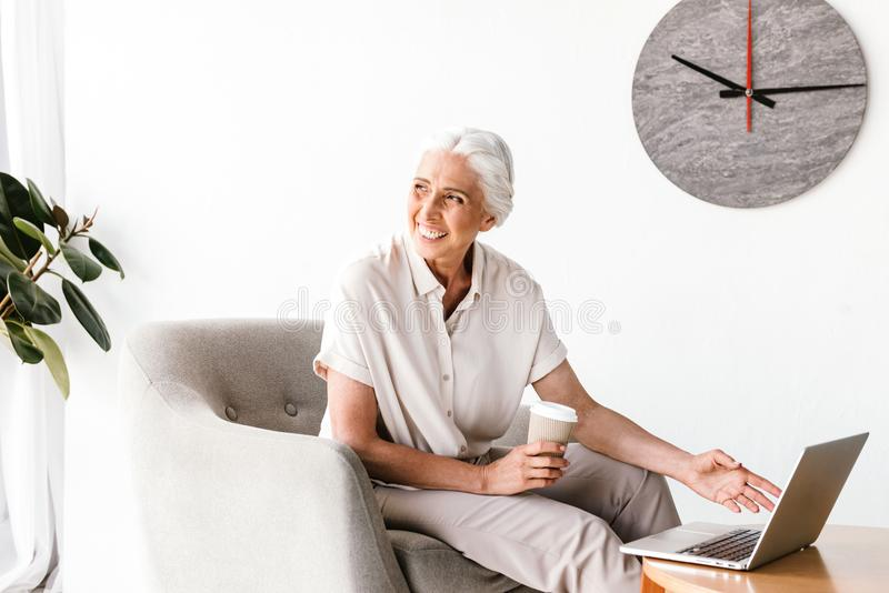 Happy mature business woman working on laptop stock images