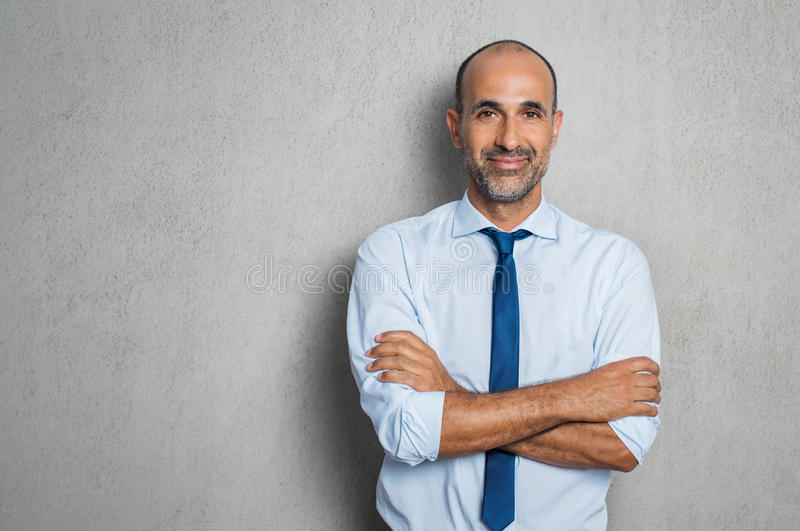 Happy mature businessman. In blue shirt and tie looking at camera. Portrait of smiling and satisfied hispanic business man with arms crossed isolated over grey stock photography