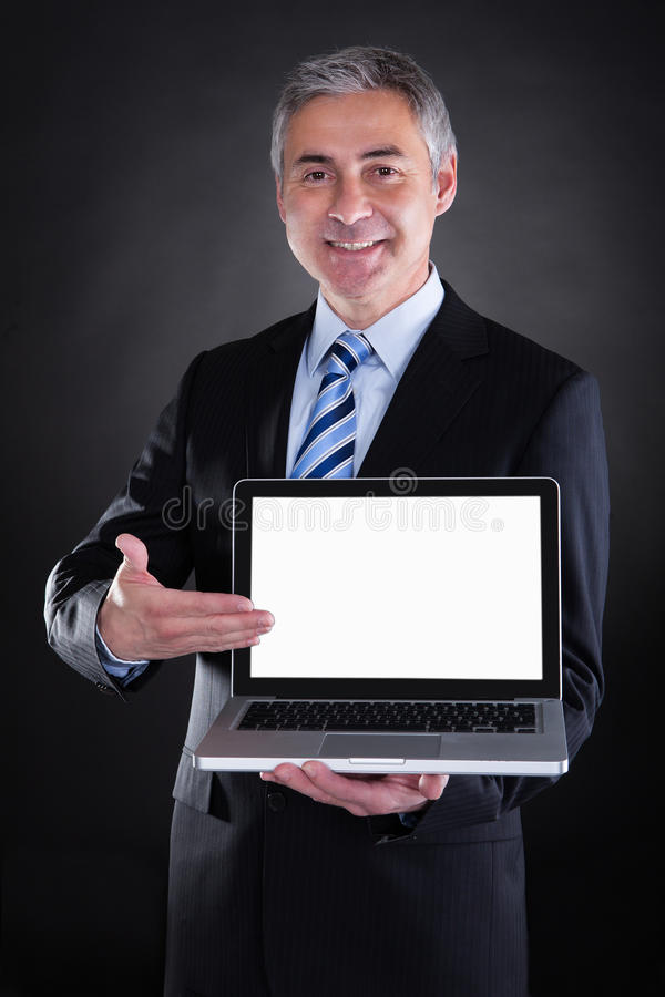 Happy Mature Businessman Showing Laptop stock images